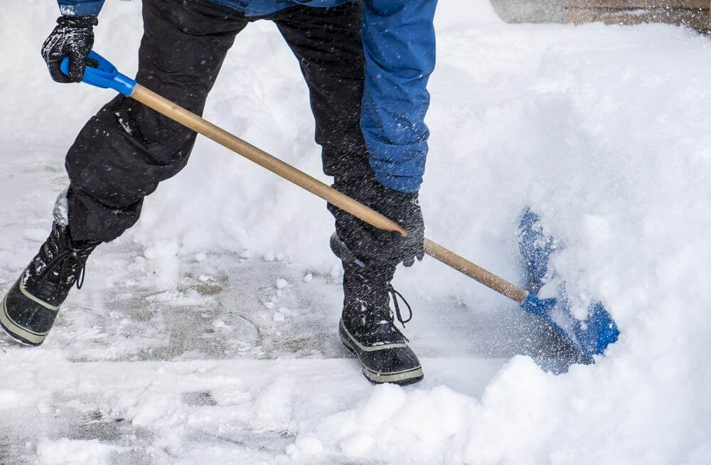 Part Man shoveling snow with blue plastic shovel