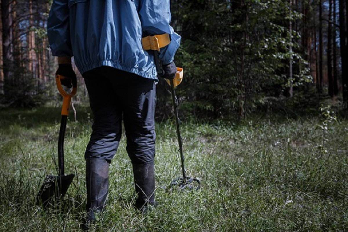 A man with a metal detector in the woods looking for vintage items and valuable coins